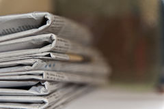 Newspapers stack. Stack of newspapers viewed on their folded ends with a dark background with a shallow depth of field with area on right hand side for text etc stock image