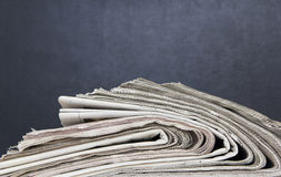 Newspapers stack. Side view on black background Royalty Free Stock Photography