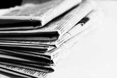 Newspapers folded Monochrome. Stack of newspapers viewed on their folded ends in black and white to simulate T Max P3200 with a shallow depth of field. Copyspace royalty free stock image
