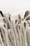 Newspapers viewed end on. With selective focus on a white background stock image