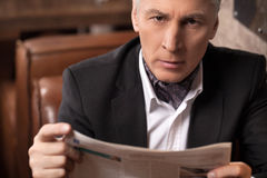 A newsworthy businessman. Confident mature businessman looking a. T camera and holding a newspaper while sitting in the restaurant Stock Photo