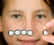 Newton's cradle. Young girl holding a pendulum ball Royalty Free Stock Photos