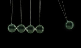 Newton's Cradle. Newtons cradle silver balls viewed from the side, all balls in a row with one moving Royalty Free Stock Photos
