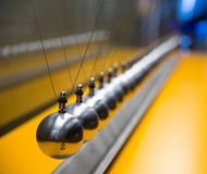 Newton's cradle. Balancing large group of balls Royalty Free Stock Image