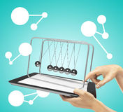 Newton's cradle. Hands holding tablet with newton's cradle Stock Photo