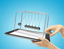 Newton's cradle and tablet. Hands holding  touch pad with newton's cradle Royalty Free Stock Photography
