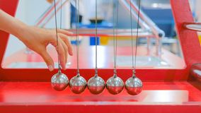 Newton`s cradle work. Interactive exposition in science museum. Demonstration of Newton`s cradle work at technology museum. Science and physics concept royalty free stock images