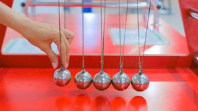 Newton`s cradle work. Interactive exposition in science museum. Demonstration of Newton`s cradle work at technology museum. Science and physics concept royalty free stock photography