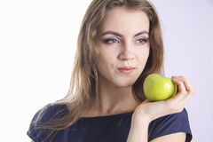 NEWTON`s Earth gravity law. Beauty girl holding green apple and sitting on wooden chair or bench stock images