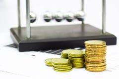 Newton-Wiegen-Stahlbalancen-Ball und Finanzberichte mit Münzen Stockfotografie