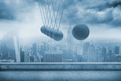 Newtons cradle above city Stock Photo