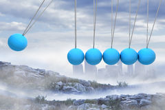 Newtons cradle above city in mountains Stock Photo