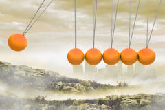 Newtons cradle above city in mountains Stock Image
