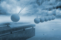 Newtons cradle above coastline. In blue Stock Images
