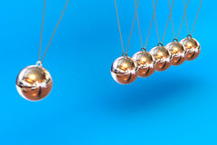 Newtons Cradle on a Blue Background. A Colourful 3d Rendered Newtons Cradle Illustration on a Blue Background Stock Photos