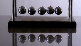 Newtons cradle in motion on reflective surface Stock Photo