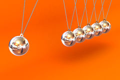 Newtons Cradle on a Orange Background Royalty Free Stock Photography