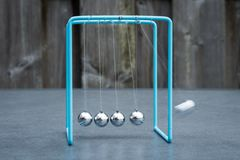 Newtons cradle, physics experiment: collision balls in action. Blurred motion. royalty free stock image