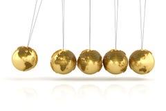 Newtons vaggar med guld- jordklot som förbi bildas Arkivbilder