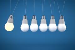 Newtons Wiegenkonzept mit Glühlampe auf blauem Hintergrund Stockbilder