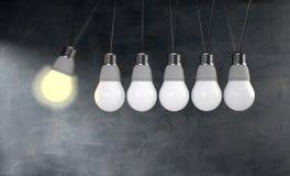 Newtons Wiegenkonzept mit Glühlampe auf blauem Hintergrund Stockfotografie