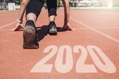 2020 Newyear, женщина спортсмена начиная на линии для начала бежать с началом 2020 к Новому Году стоковое фото