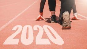 2020 Newyear, женщина спортсмена начиная на линии для начала бежать с началом 2020 к Новому Году стоковое изображение