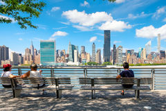 NewYorkers at a park in Queens with a view of midtown Manhattan. New YORK,USA - AUGUST 21,2016 : NewYorkers relaxing at a park in Queens with a view of the Royalty Free Stock Photo