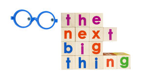 The Next Big Thing. Concept spelled with colorful toy blocks with interested googly eyes set inside blue plastic frames. Isolated Stock Photos