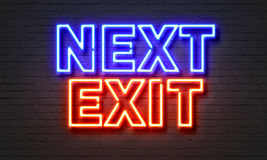 Next exit neon sign on brick wall background. Stock Photos