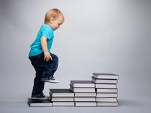 Next grade. A toddler climbing on a steps made of books Stock Images