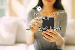 Next level concept with woman using a smartphone royalty free stock photos