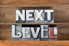 Next level tray. Next level phrase made from metallic letterpress type on wooden tray Stock Photo