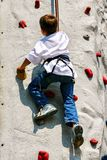 Boy enjoying indoor rock climbing stock images