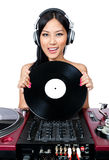 And the next record is. A young female Asian DJ holding a record while standing in front of a mixer and turntables Royalty Free Stock Photo