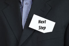 Next step text concept. Next step text note concept over businessman background Stock Images