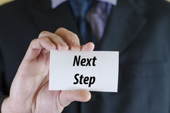Next step text concept. Next step text note concept over businessman background Royalty Free Stock Image