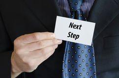 Next step text concept. Next step text note concept over businessman background Royalty Free Stock Photography