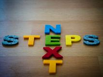 Next steps concept in colorful letters. On wooden blackboard Stock Photo