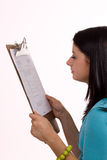 The Next Task. Young woman looking at a document on a clipboard Stock Photos