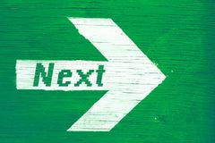 `Next` text written on a white directional arrow painted on a green wooden signboard background. Royalty Free Stock Image