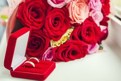 Next to the bouquet of the bride lies a pair of gold wedding rings in a red velvet box. royalty free stock photo