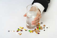 Next to the glass scattered pills stock image