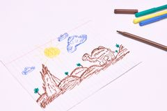 Next to the markers is a primitive children`s drawing with a felt-tip pen on a white background. child development stock photo