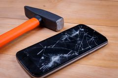 Next to a smartphone with a broken screen is a hammer. On a wooden background. Close-up. Next to a modern black smartphone with a broken screen is a heavy stock images