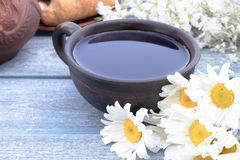 Next to the white flowers of chamomile is a cup of tea royalty free stock images