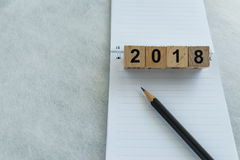 Next year goals or target concept with wooden blocks number 2018. And pencil on white note paper with copy space Royalty Free Stock Images