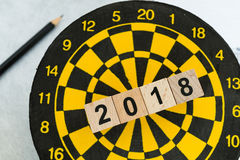 Next year planning target concept with wooden blocks number 2018. On dart board and pencil Royalty Free Stock Images