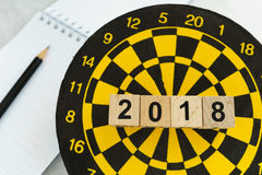 Next year planning target concept with wooden blocks number 2018. On dart board and pencil Stock Image
