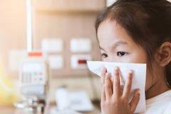 Nez de essuyage et de nettoyage de fille asiatique malade d'enfant avec le tissu Image libre de droits
